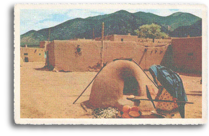 A Native American woman prepares food in a horno (adobe oven), with Taos Mountain and the some of the dwellings of the historic Taos Pueblo visible behind her. Even today, tourists can enjoy fresh-baked fry bread during their visit to the 1,000-year-old Taos Pueblo, just north of the town of Taos, New Mexico.